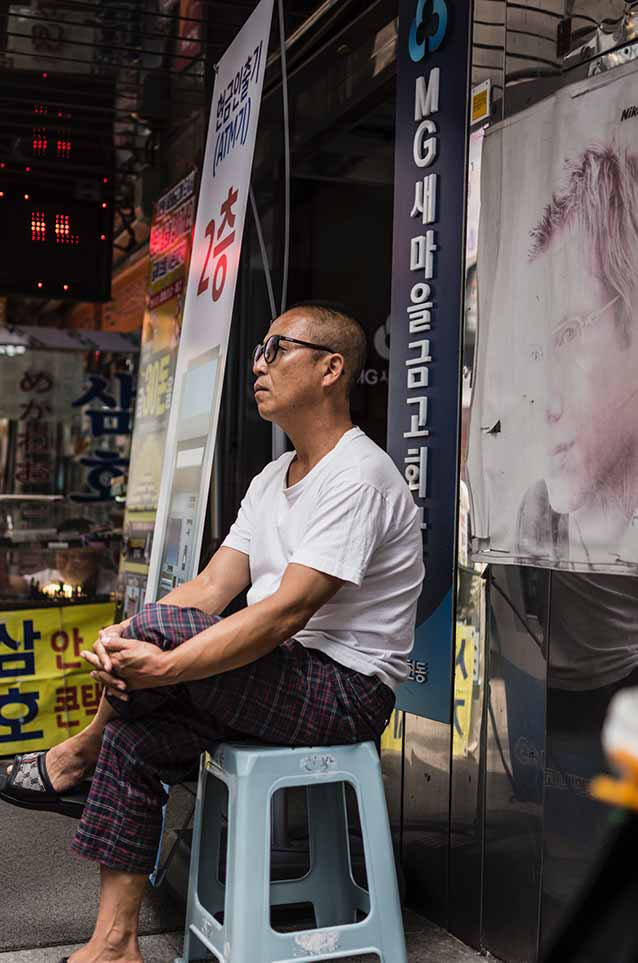 where to stay in ho chi minh city: old korean guy sitting outside