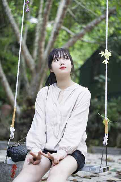 Vietnamese girl sitting on a swing waiting for someone