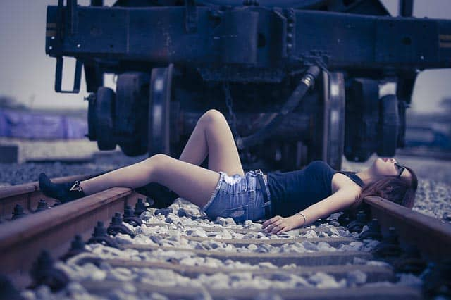 Girl lying on train tracks