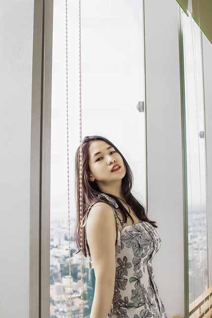 Vietnamese girl leaning against the window