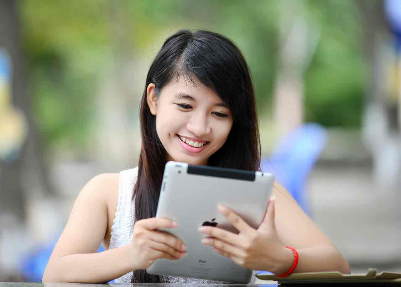 Asian girl playing on tablet