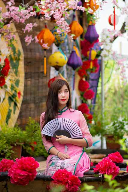 long distance dating: Vietnamese girl in pink dress with fan in hand