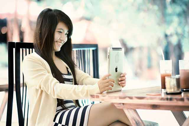 Asian girl playing on her tablet