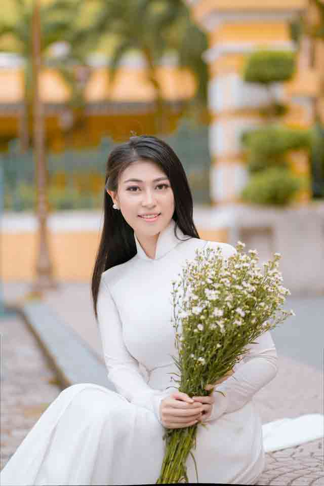 Beautiful Vietnamese girl in a white dress holding flowers
